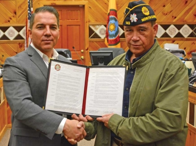 Kina Swayney's husband Doug (right in right photo) shakes hands with Principal Chief Richard Sneed while holding the newly approved resolution honoring her as a Cherokee Beloved Woman. Holly Kays photo