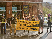 Demonstrators braved a brief downpour to advocate for the Green New Deal on                 Sept. 9 in Sylva. Cory Vaillancourt photo