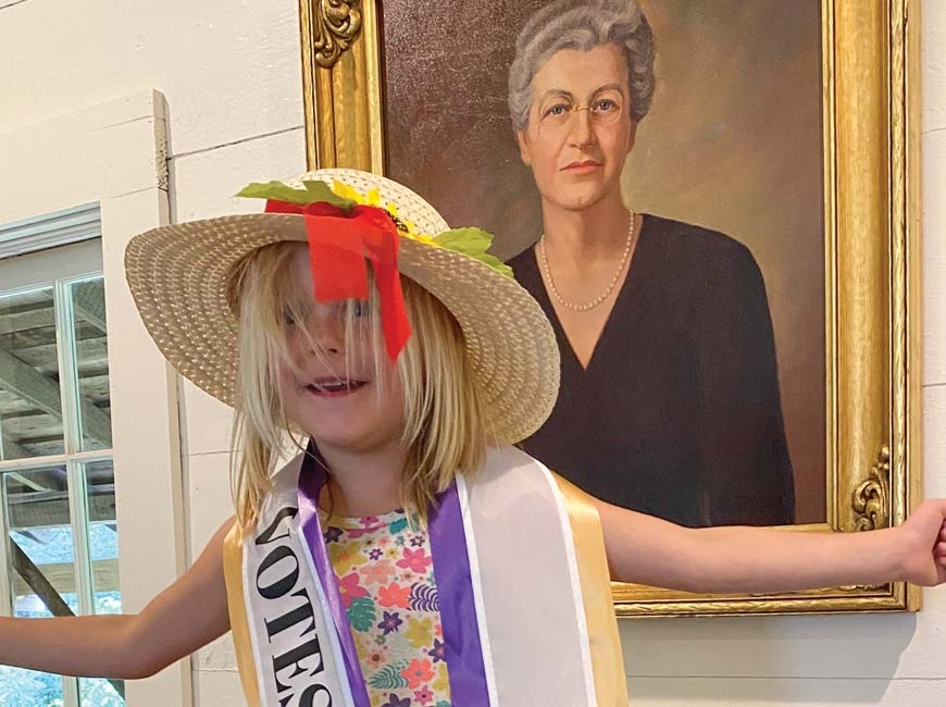 Petra Ann Austin, great-great-granddaughter of Gertrude Dills McKee, sports a suffragette sash in front a portrait of McKee displayed in the Cashiers Historical Society's XIX Amendment Exhibit. Donated photo