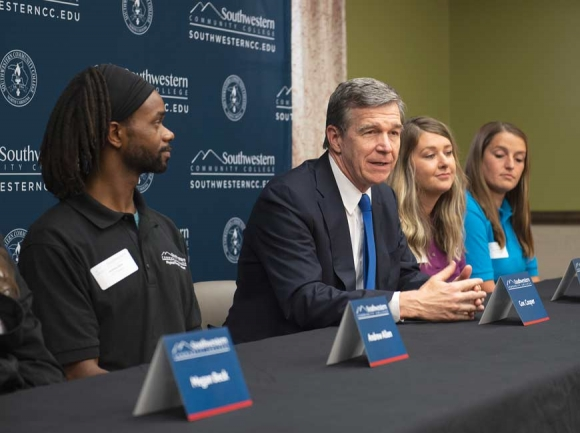 Gov. Roy Cooper (center) with Finish Line Grant recipients Andrew Allen (left) and Abbie Turner (right).