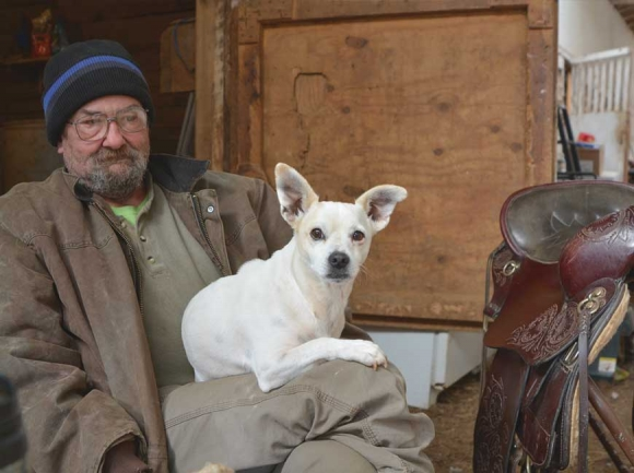 Weeping Cherry Stables operator James Lunsford sits in his barn with one of his dogs, Powder. Cory Vaillancourt photo
