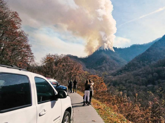Smoke billows from the Chimney Tops during the early days of the fire that would eventually sweep a path of destruction through Gatlinburg and Pigeon Forge. NPS photo