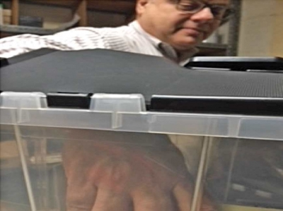 "A photo from the Veriti report shows an investigator demonstrating how easily some of the ""secure"" ballot boxes can be accessed. Donated photo"