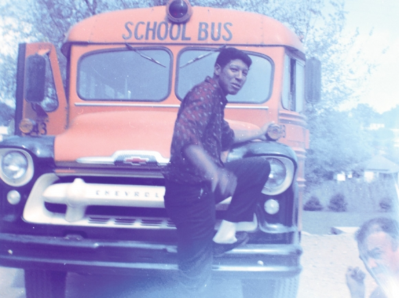 In an undated photograph developed from film brought to George Dexter Sherrill's Waynesville studio for developing in the early 1900s, an African American man leans on a school bus. Hunter Library, Western Carolina University photo