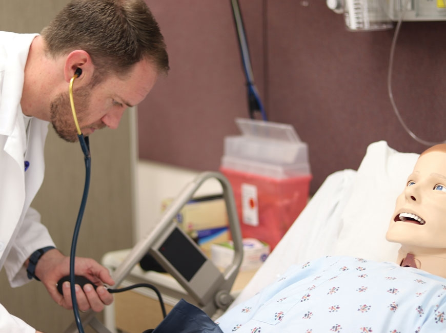 A nursing student at Haywood Community College practices his skills on a                        simulation lab dummy. HCC photo