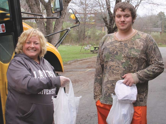 Angela Lunsford, principal of Jackson Community School, helps deliver meals to students this week. She is assisted by JCS senior Ryan Bailey. Donated photo