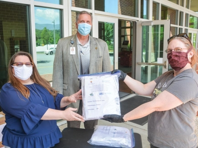 Lori Bailey, executive director of the Nantahala Health Foundation, (from left) poses with a package of masks alongside SCC President Dr. Don Tomas and Paige Christie, director of The Community Table in Sylva.