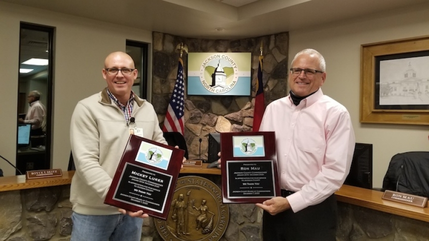 Outgoing commissioners Ron Mau (right) and Mickey Luker receive plaques commemorating their service. Chairman Brian McMahan (left) holds the plaque for Luker, who attended the meeting virtually. Jackson County photo